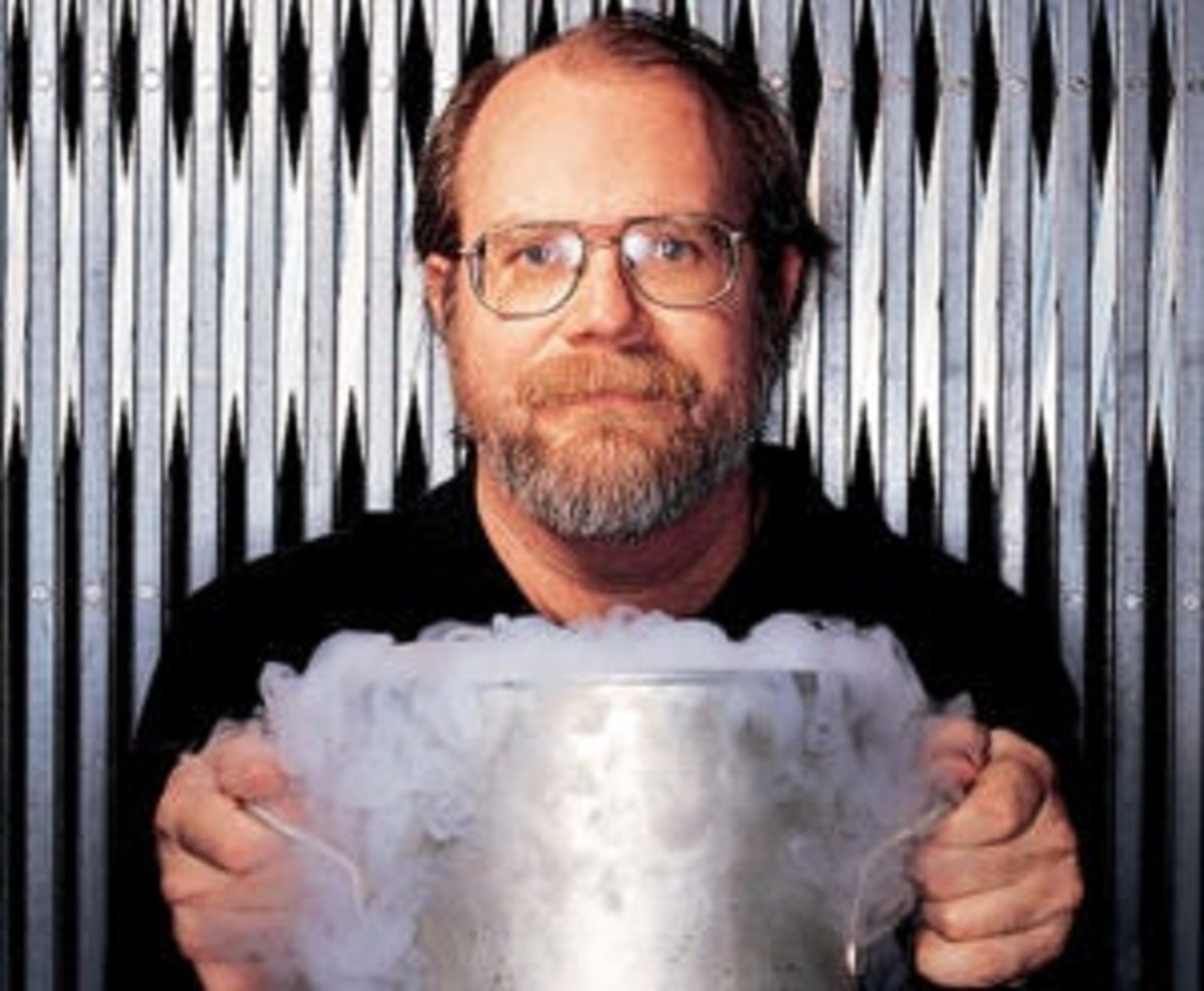 Chemist Theodore Gray holding a smoking steel vat