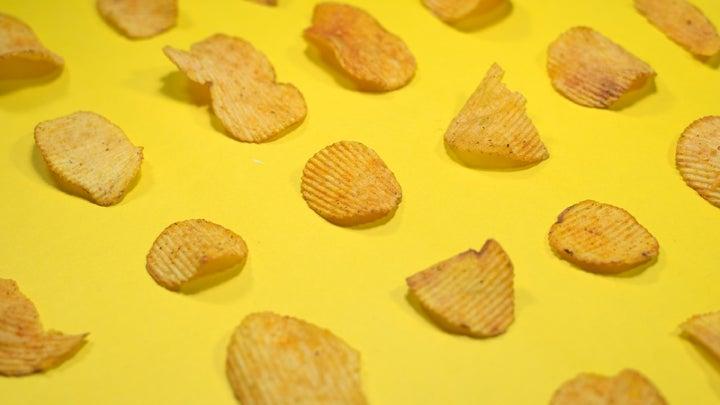 Salty ridged potato chips on yellow background