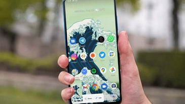 A hand holding an Android phone and taking a screenshot while outdoors in a park.