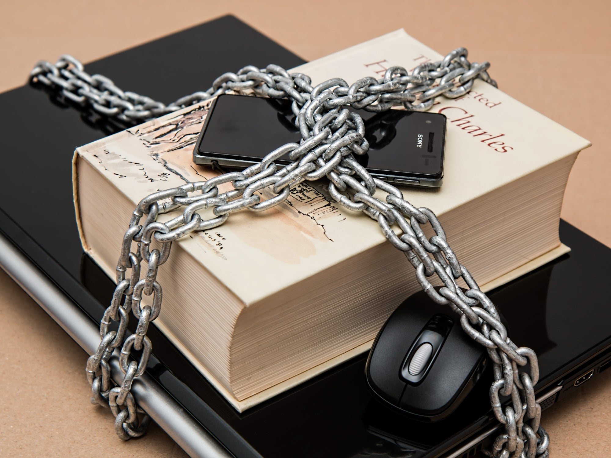 A closed laptop with a book, a mouse, and a phone on top of it, all chained together.