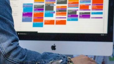 A person wearing a denim jacket using a very full Google Calendar on an Apple desktop computer.