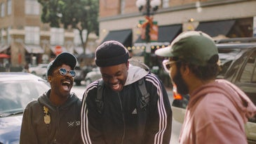 Two people laughing while talking to another person on a city sidewalk by some parked cars.