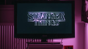 A TV with the Stranger Things title screen on it, in a dark room bathed in purple light.
