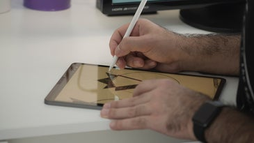 A person using a stylus on a tablet to draw an image.