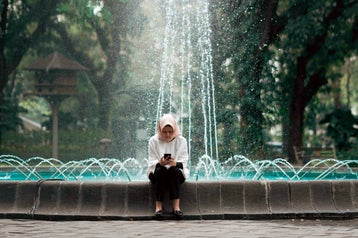 A woman sitting at the edge of an ornate park fountain, looking at a phone.