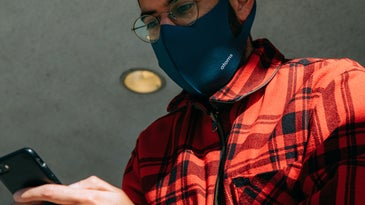 A person using their phone while wearing a face mask and wearing a red plaid shirt.