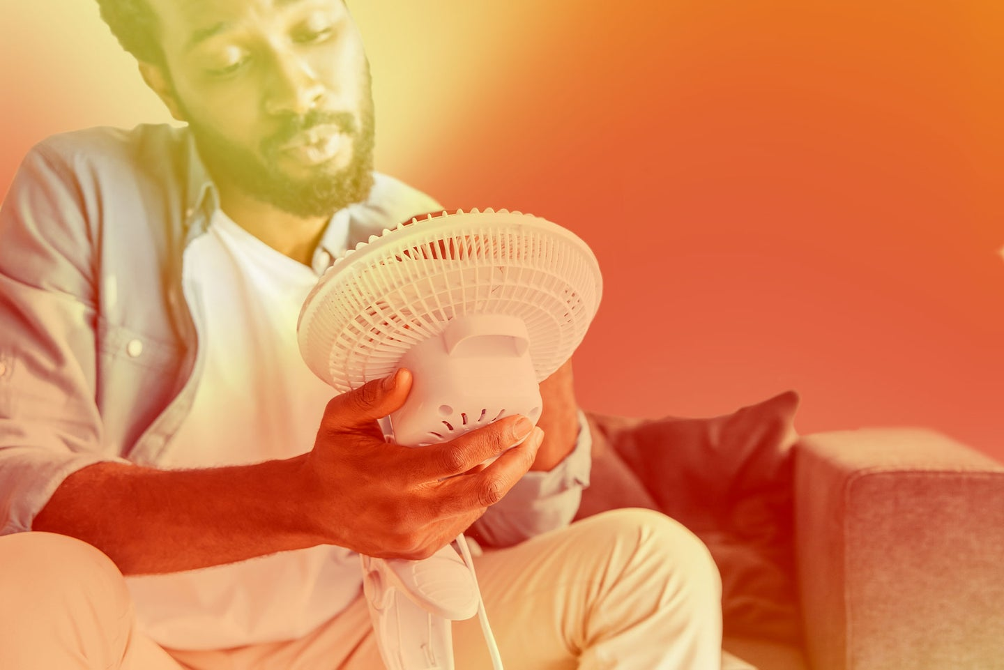 A man sitting and holding an electric fan in front of his face.