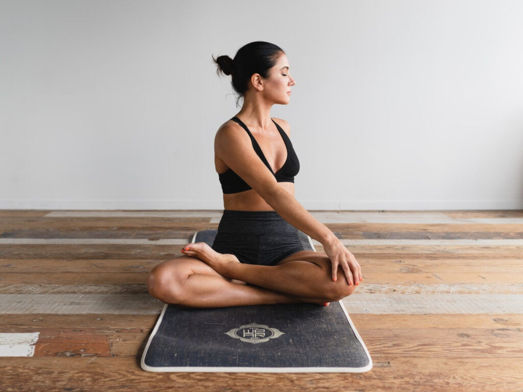 A woman sitting cross-legged on a yoga mat, rotating her torso to stretch her back.