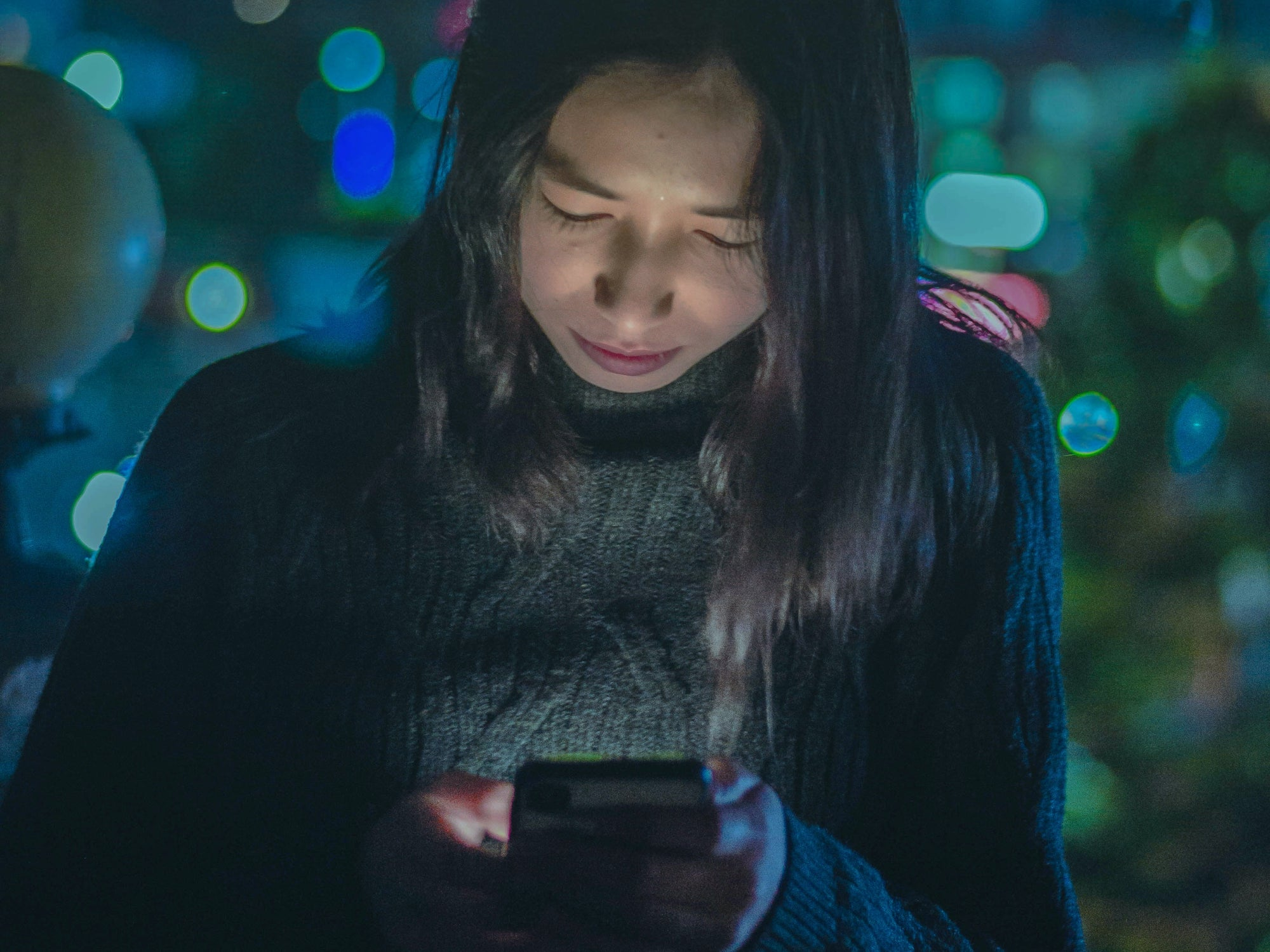 A woman looking at her phone screen at night while the screen illuminates her face