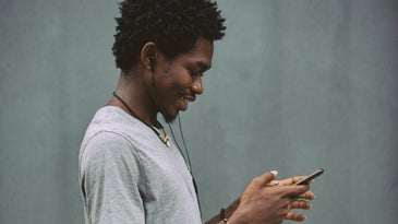 A person using finger gestures on their phone while wearing headphones and standing in front of a gray wall.