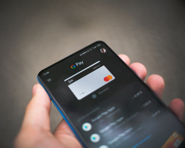Google Pay on a smartphone screen in a person's hand