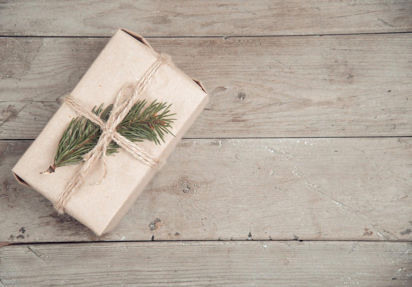 a gift wrapped in brown paper and leaves