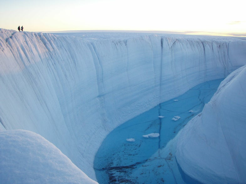 a large ice canyon with deep blue melted water in the middle