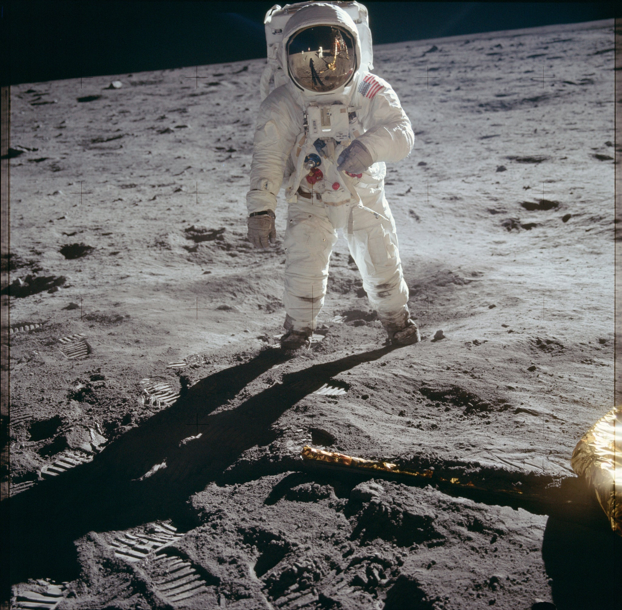 an astronaut stands on the gray surface of the moon in a spacesuit