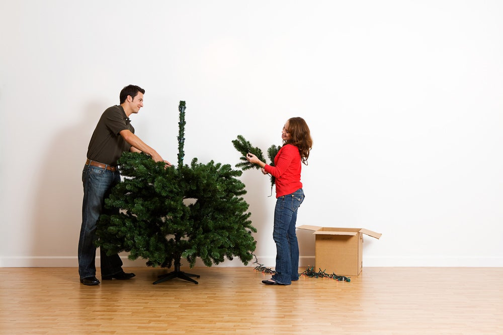 couple building an artificial christmas tree