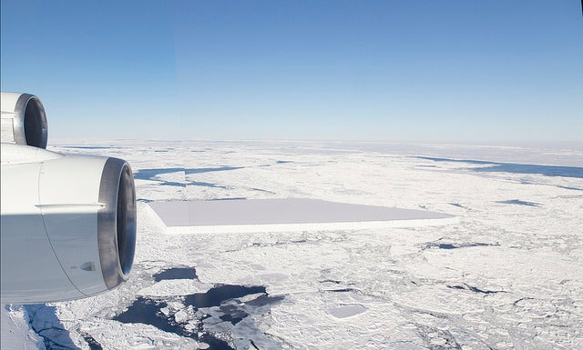 Aerial shot of a flat, rectangular iceberg floating in a sea of smaller pieces of ice.