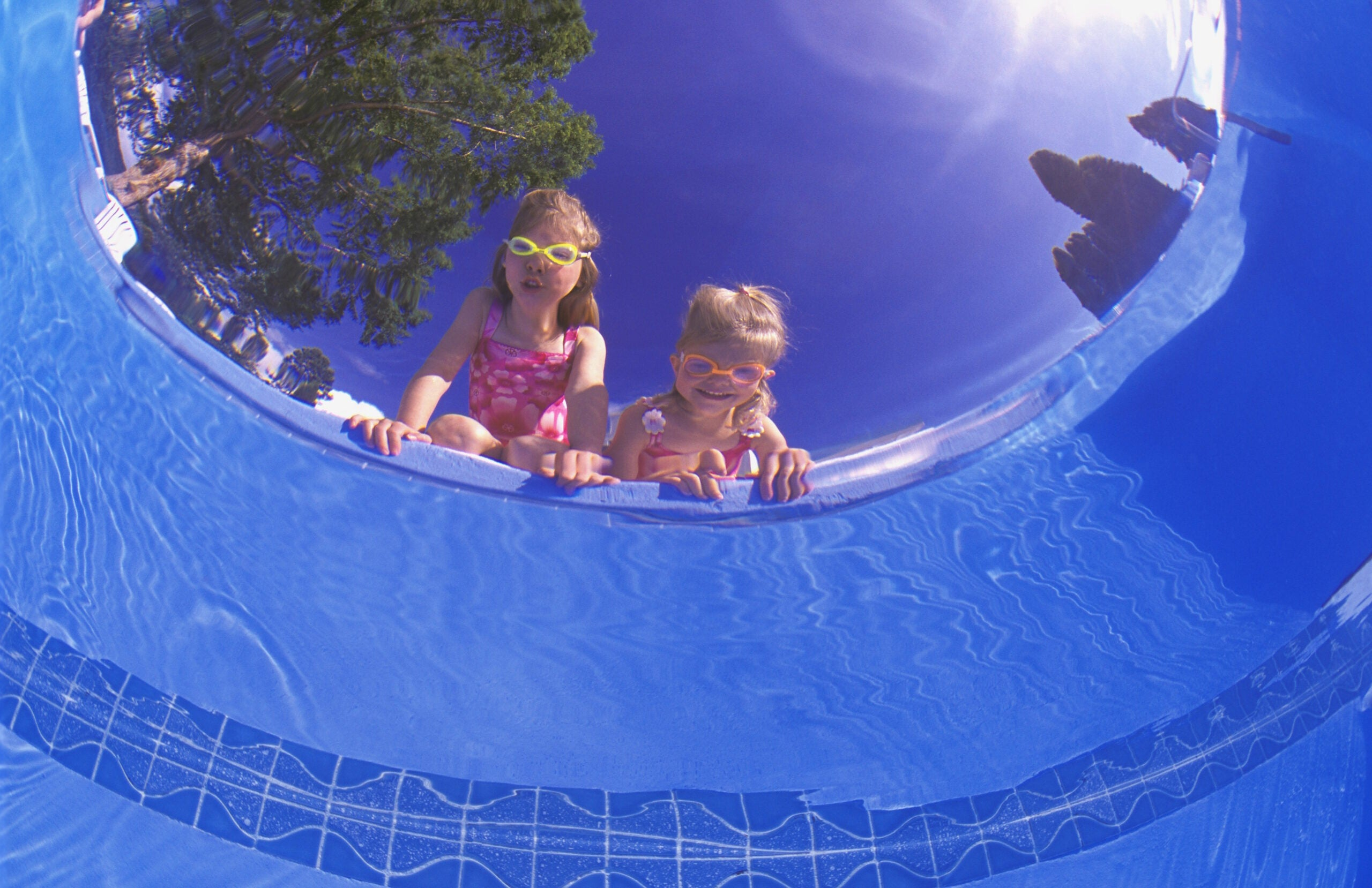 two kids stare down into a pool