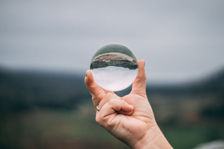 a hand holding a glass sphere