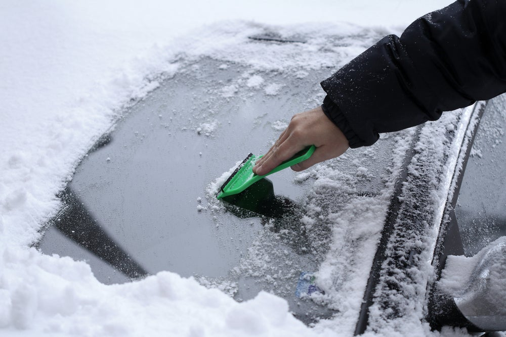 scraping ice and snow off a car windshield