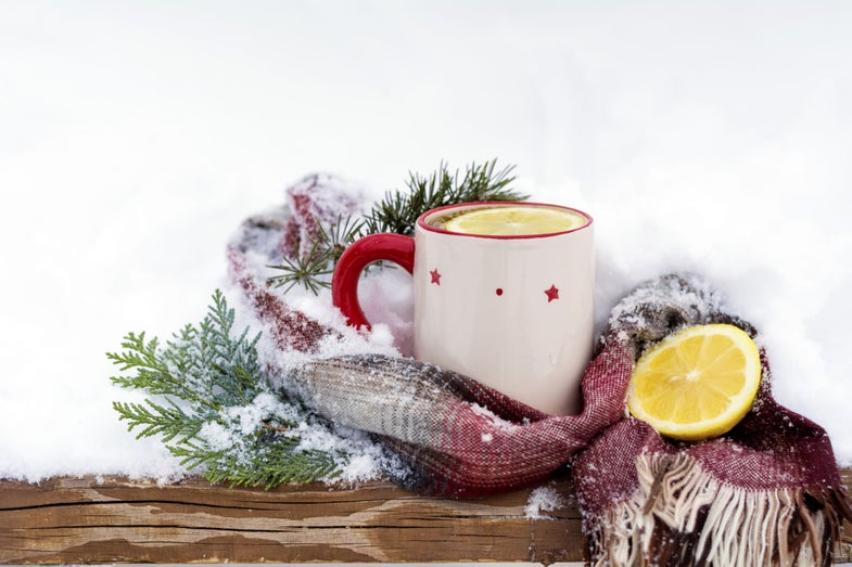 a mug with lemons and tea sitting on a snow-covered table
