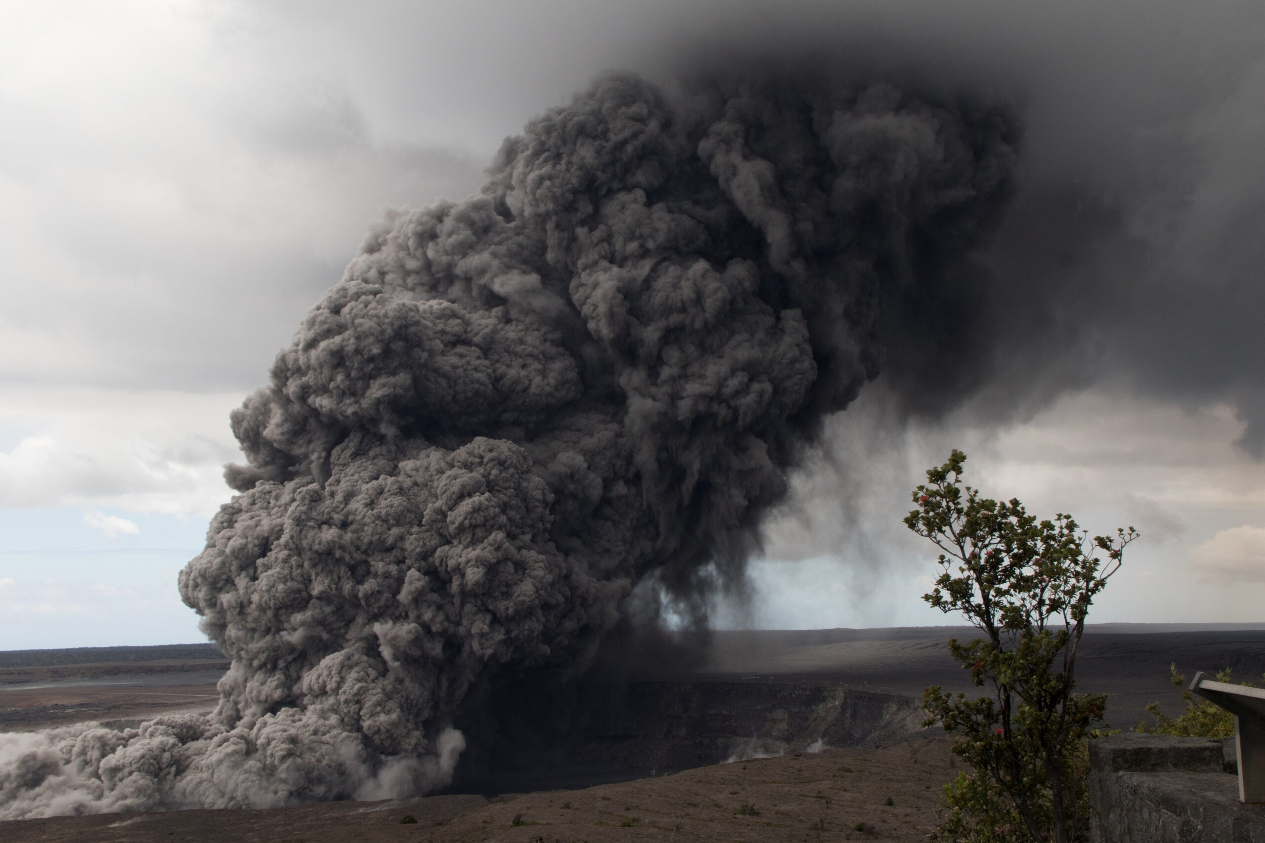 cloud of dark smoke rising out of the ground towards white clouds