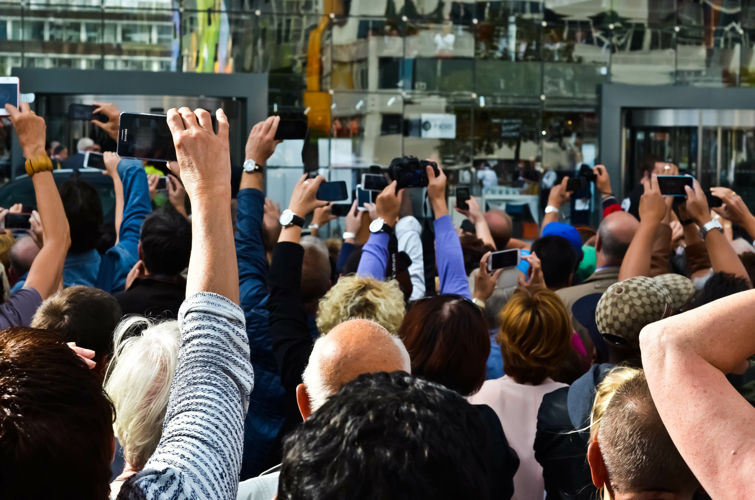 people holding up phones in crowd to take photographs