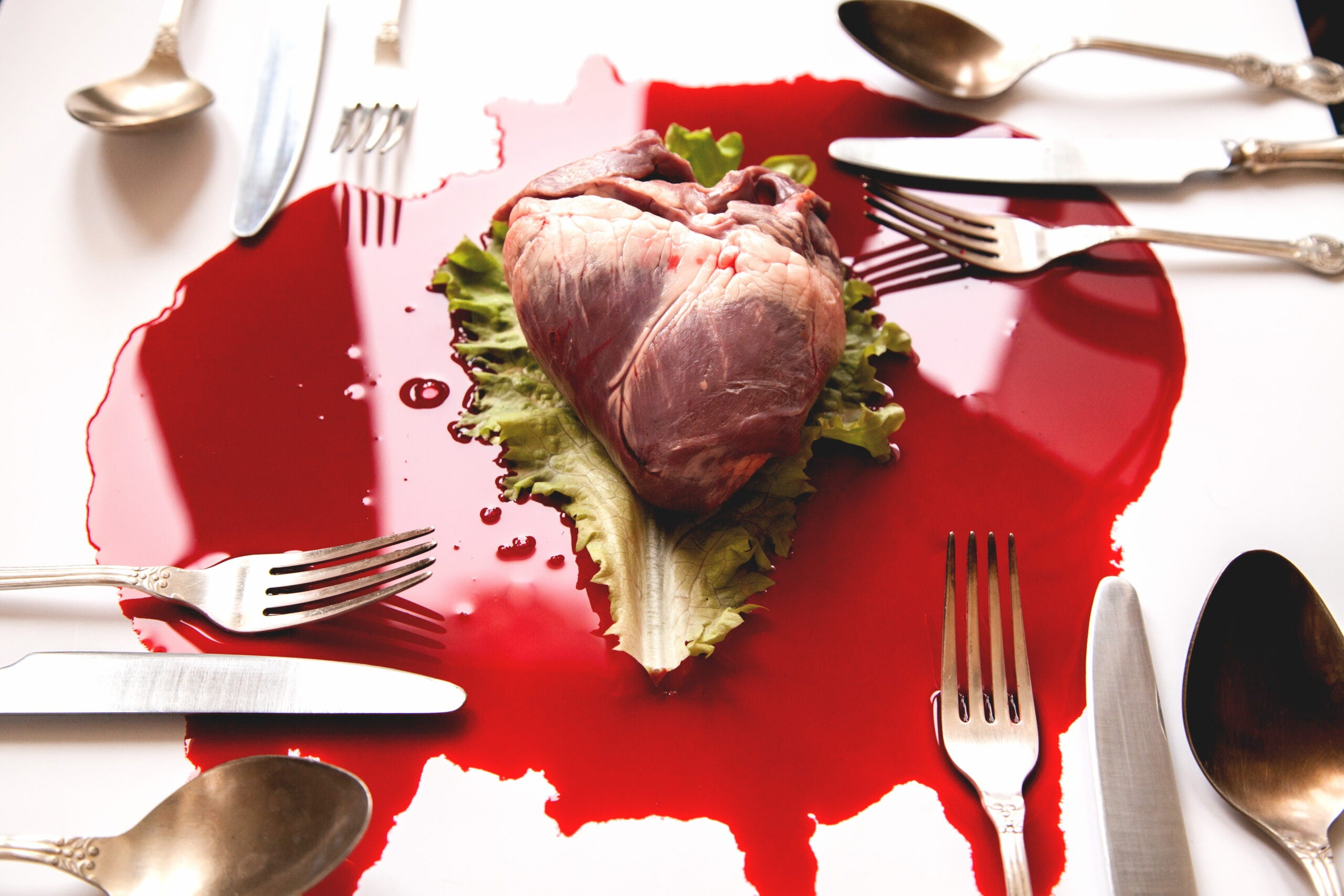 a bloody heart surrounded by forks