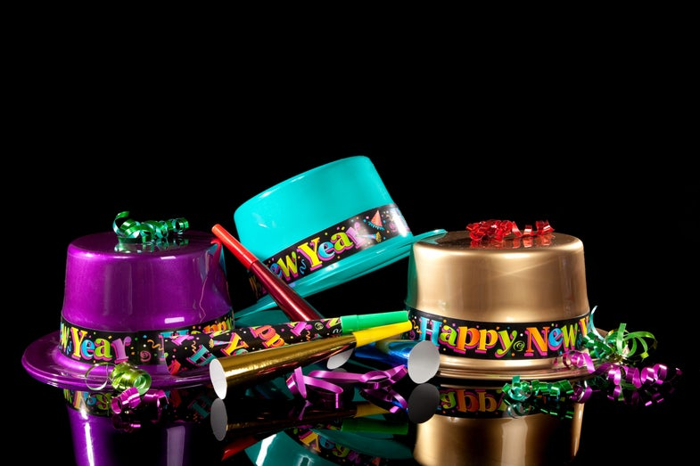 three colorful plastic hats that say happy new year on a black background with noisemakers and ribbons
