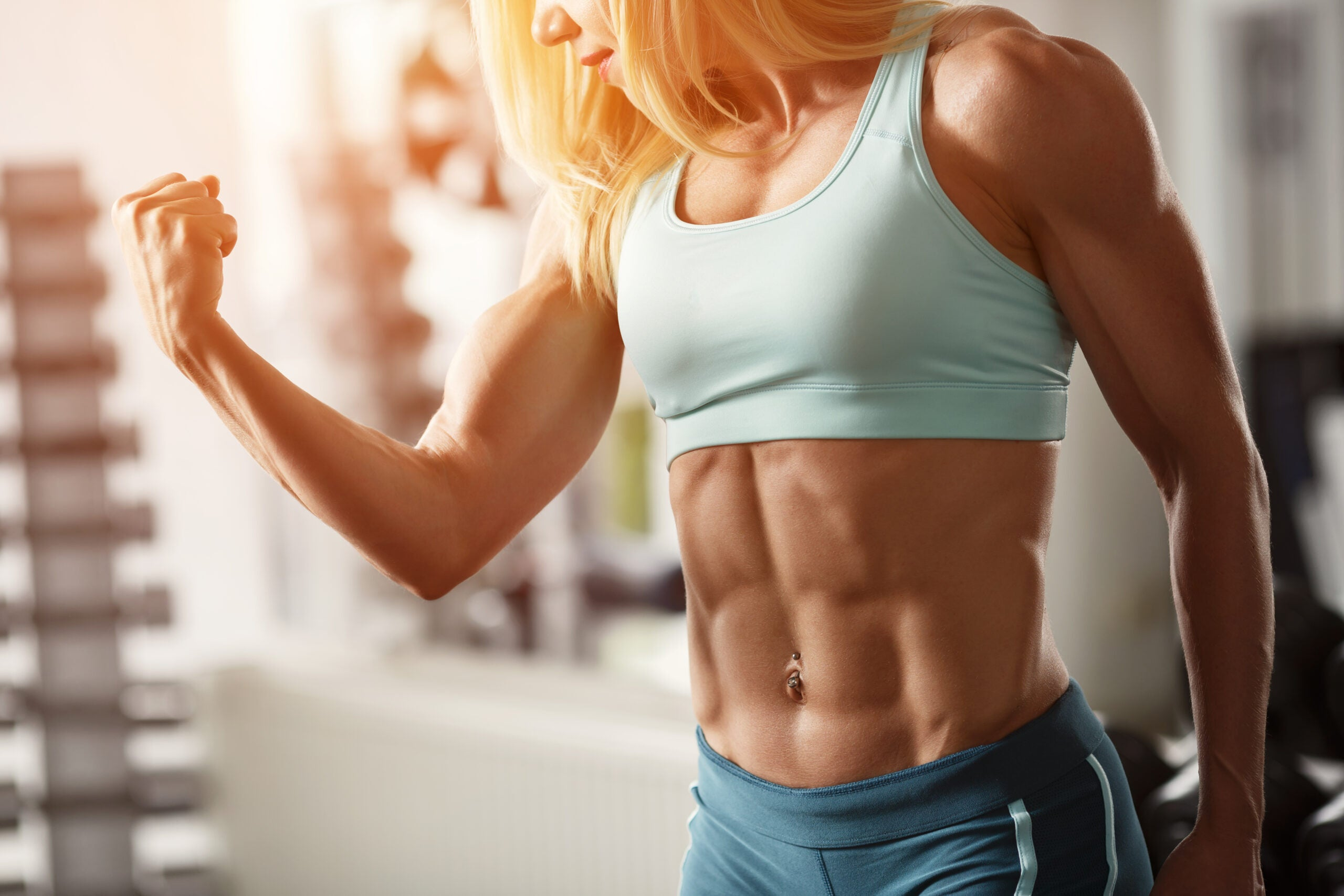 a blond woman with lots of muscles flexes for the camera