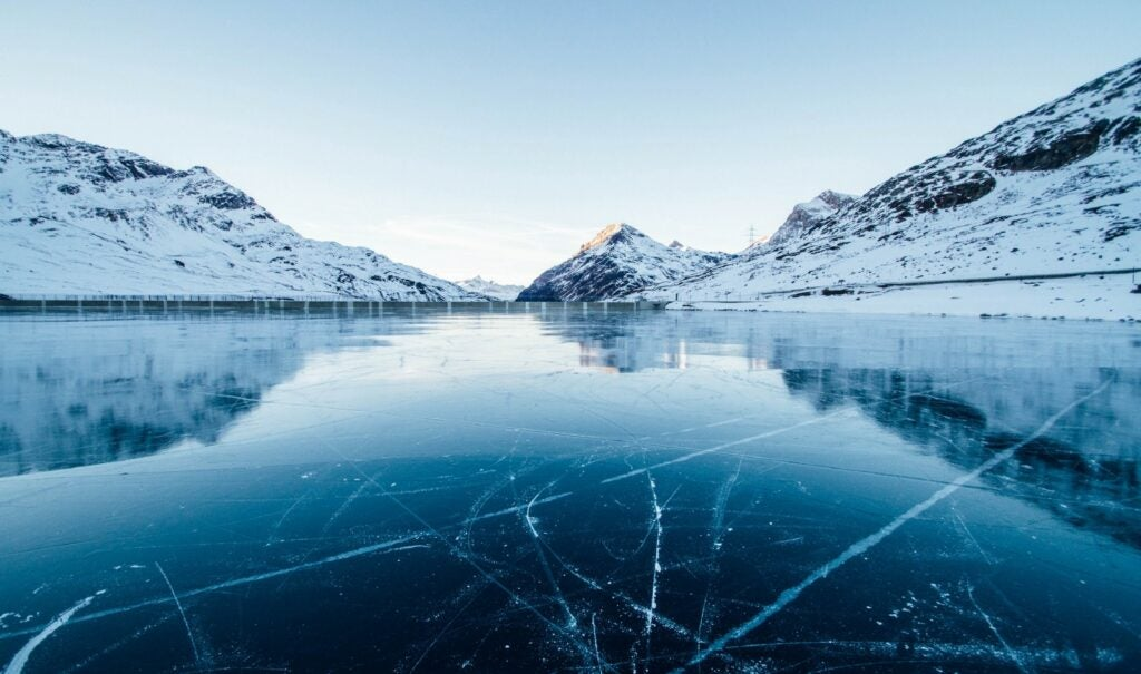 ice cracking in a body of water surrounded by snowy mountains