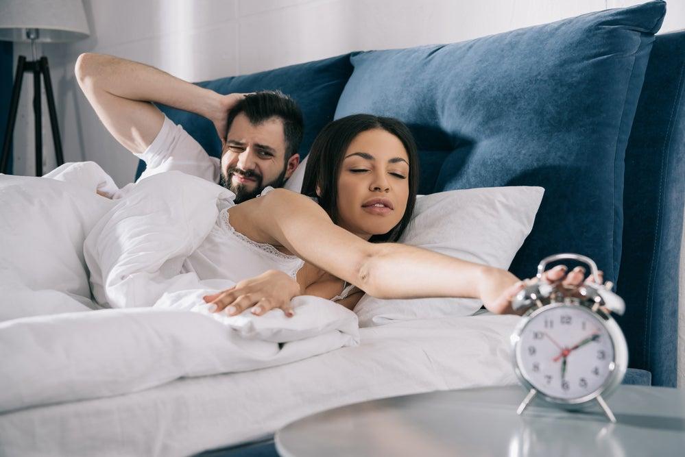 couple waking up to alarm