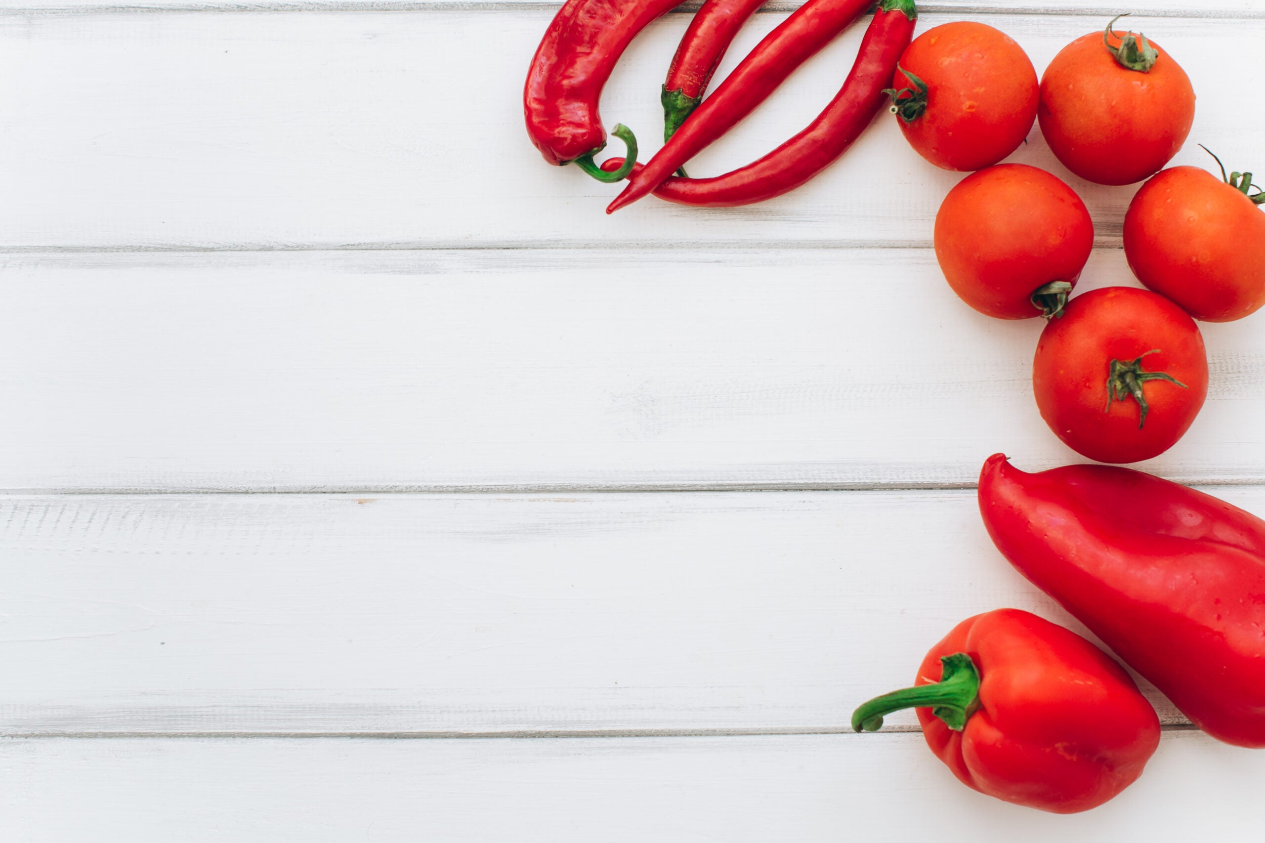 tomatoes and red peppers on a white table