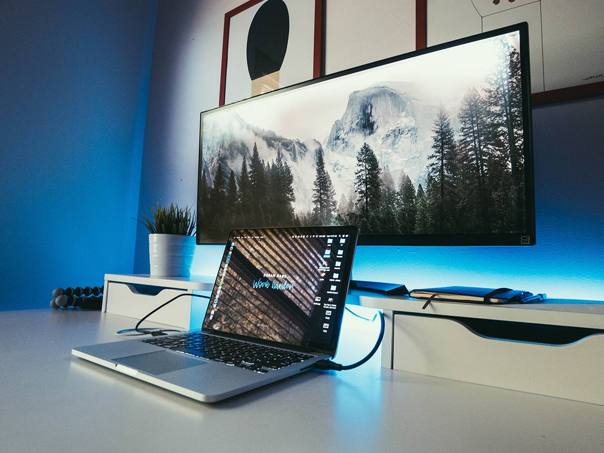 A 2-monitor setup with a laptop hooked up to a much larger external monitor while sitting on a white desk in a blue room.