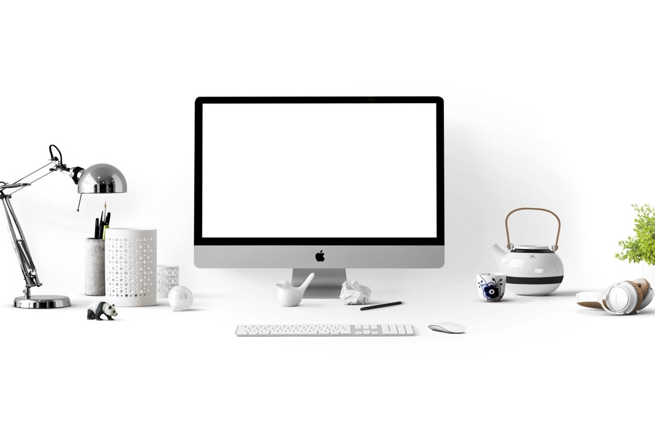 an Apple Mac computer on a desk against a white background