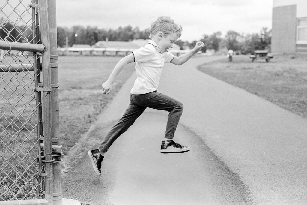 Black-and-white photo of boy leaping into the air
