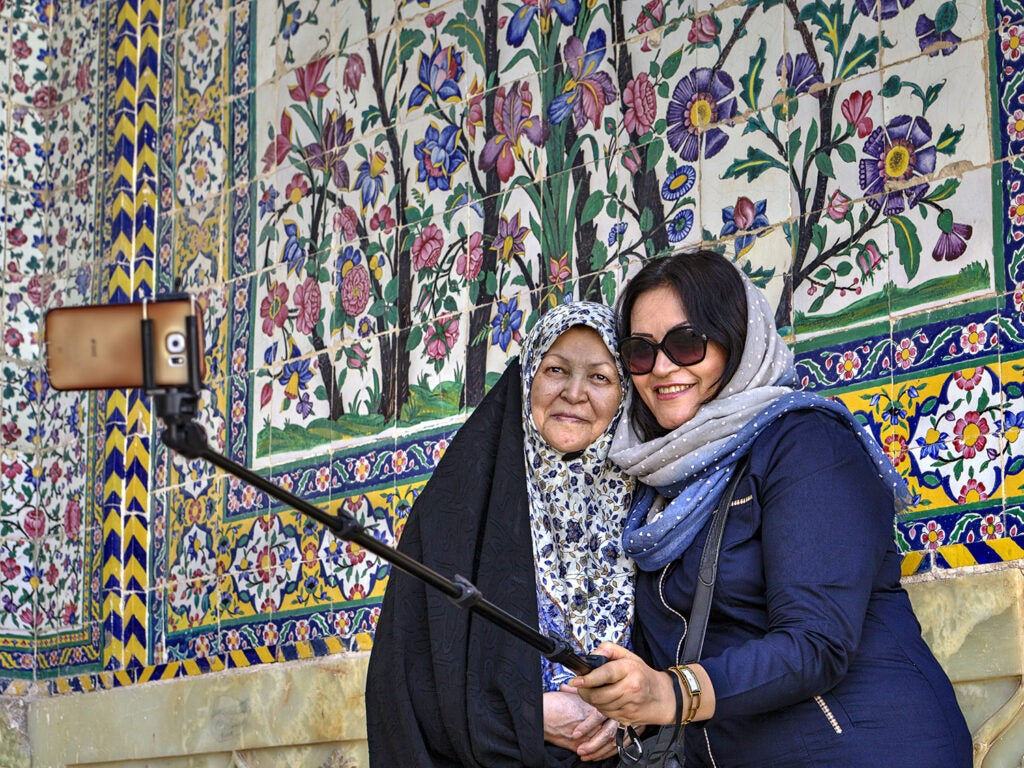 women taking pictures in front of mosaic