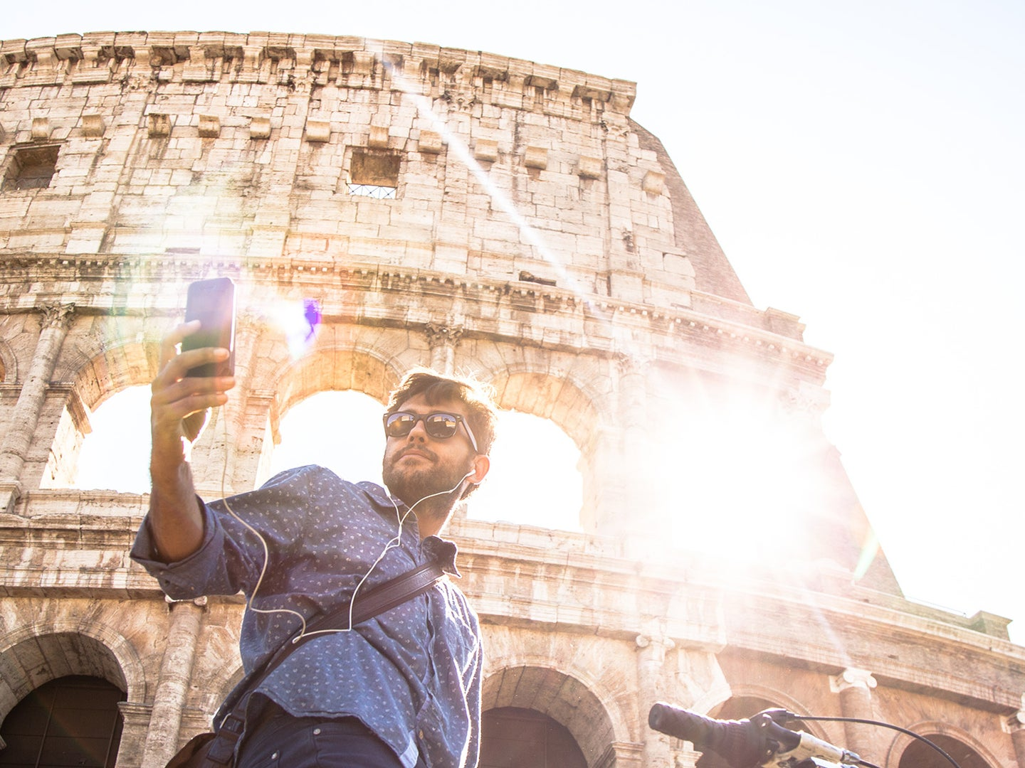 man snapping selfie in front of the Colisseum