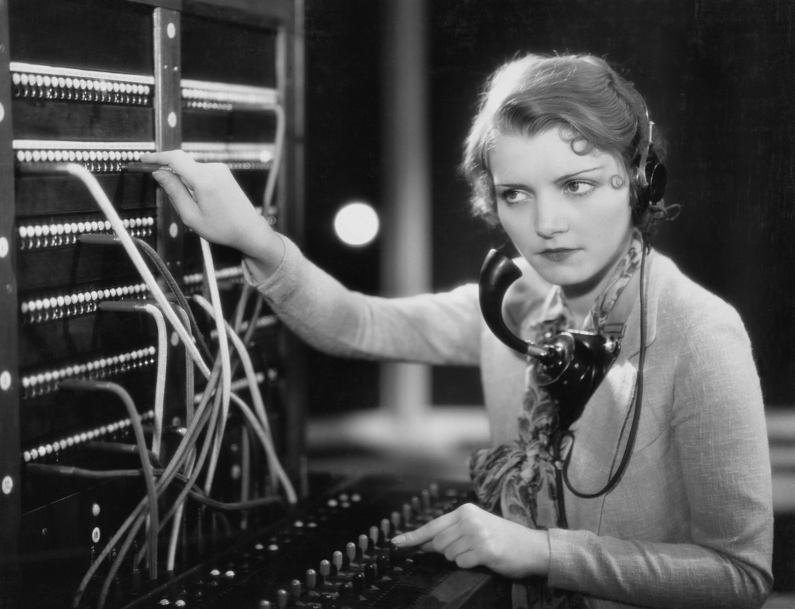 a woman at a switchboard listening