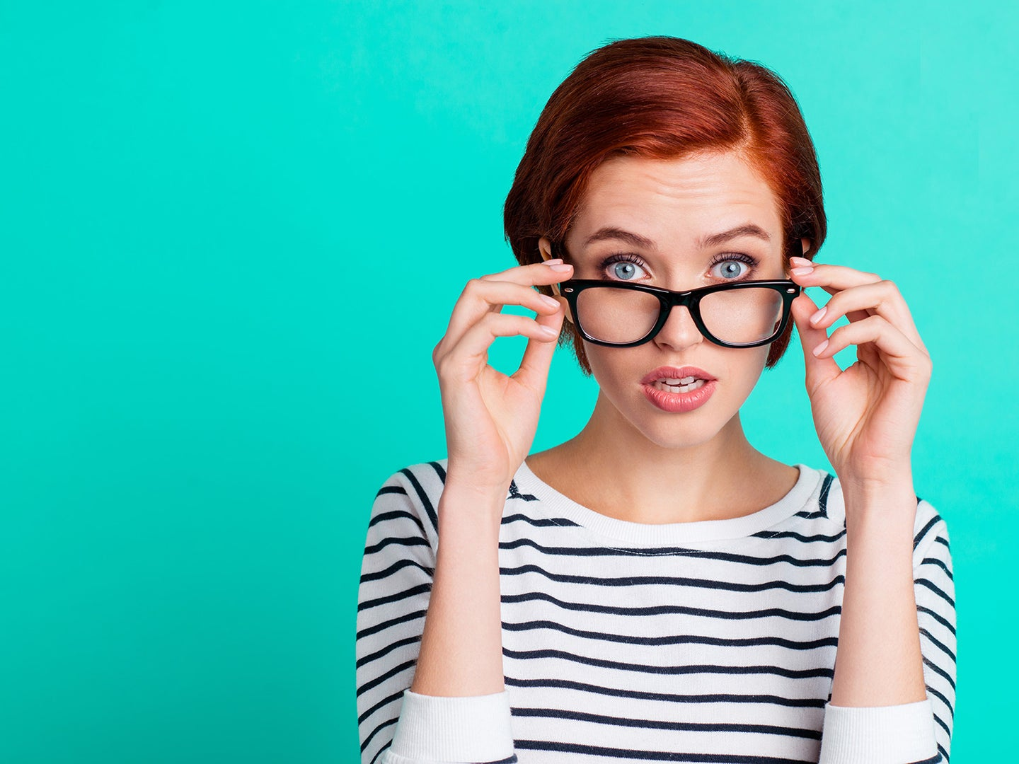 blue eyed woman pulling down glasses