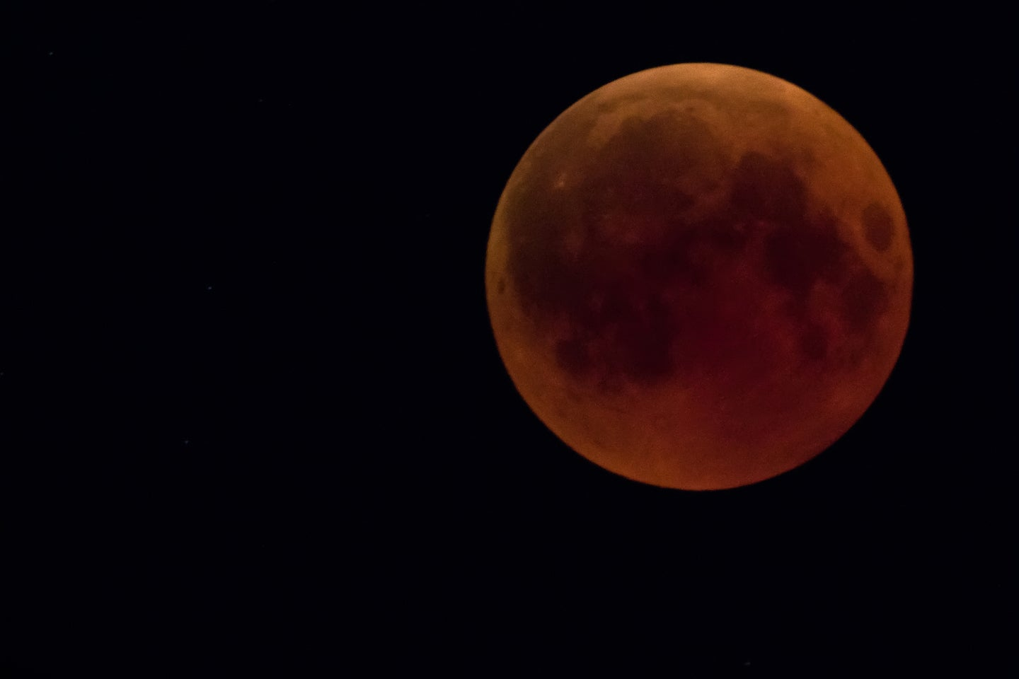 a moon with a red tint due to a lunar eclipse
