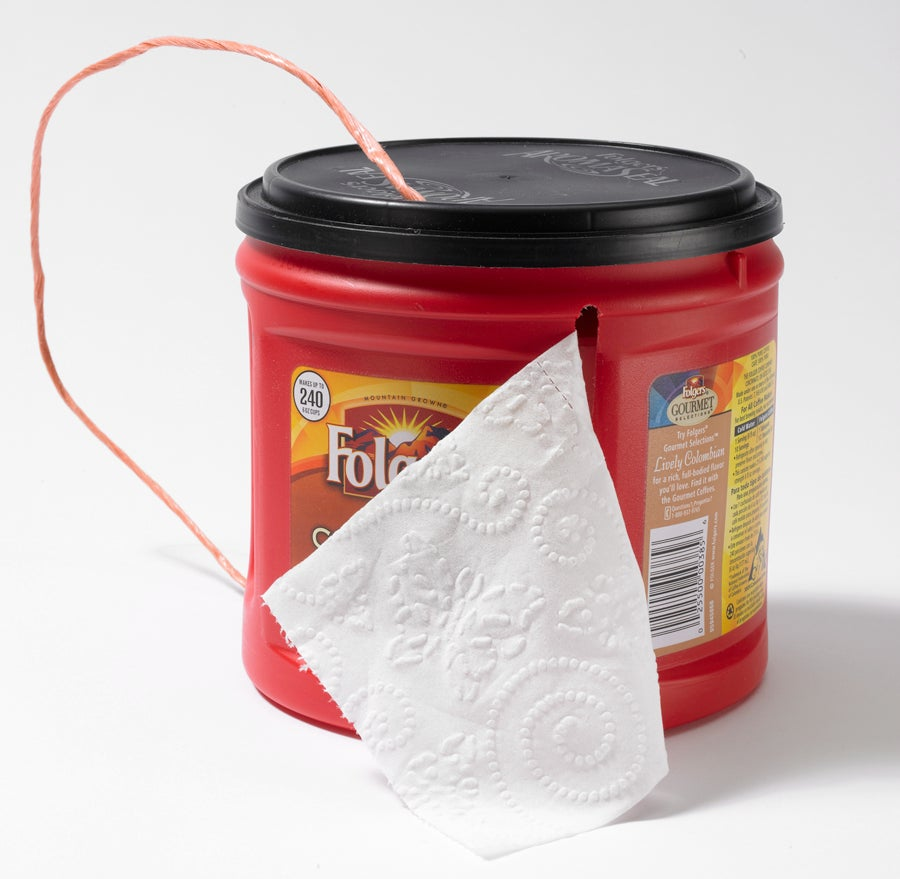 A foldgers coffee cup used as a toilet paper holder.
