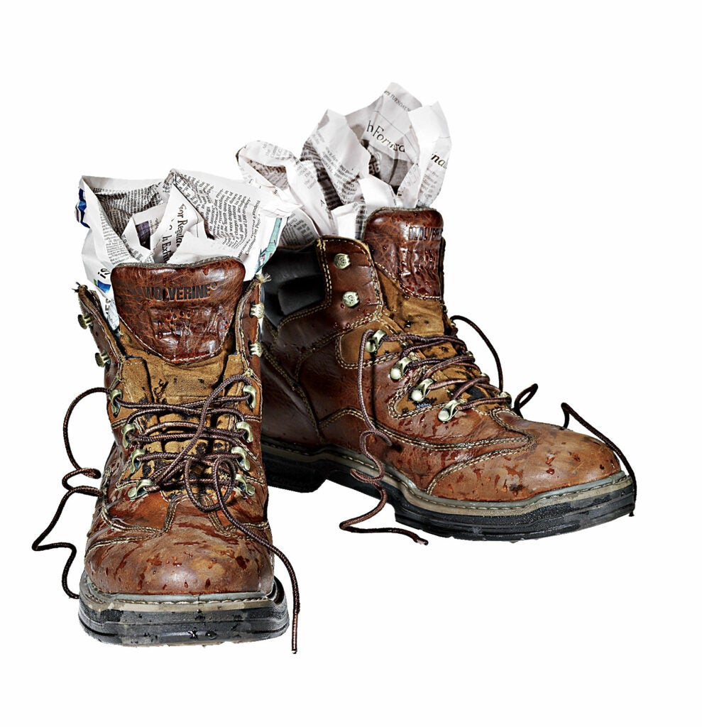 A pair of boots with newspaper stuffed in them.