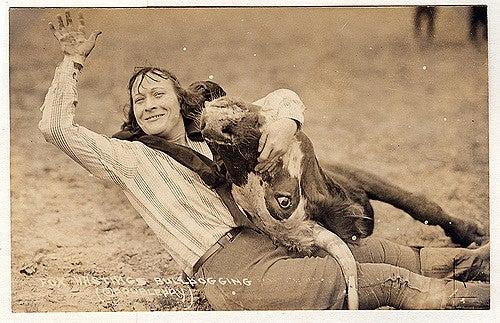 a woman wrangling a cow