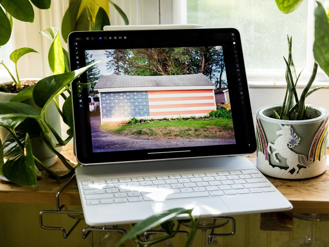 An iPad Pro with a keyboard, on a windowsill surrounded by plants and bathed in sunlight.