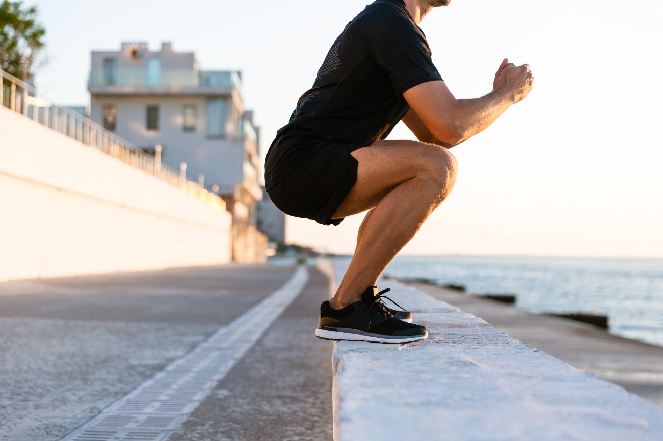 a man doing a squat on a beach