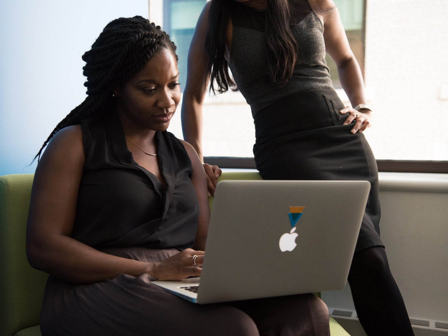 A woman using an Apple Macbook laptop while another woman watches from nearby.