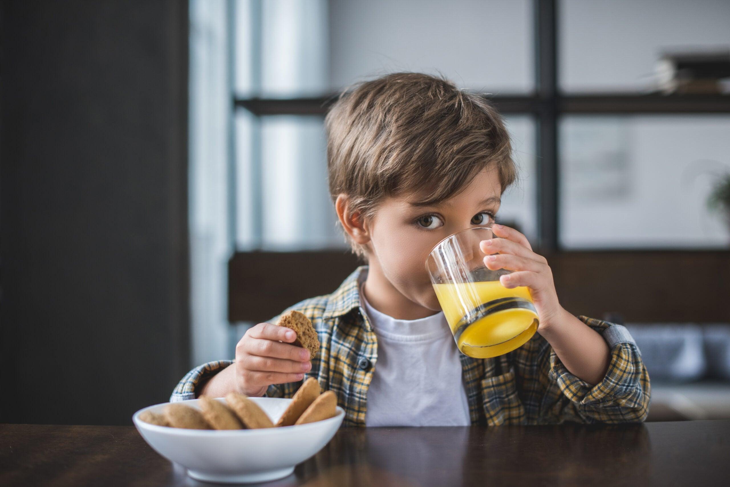 a young boy drinks juice and eats cookies