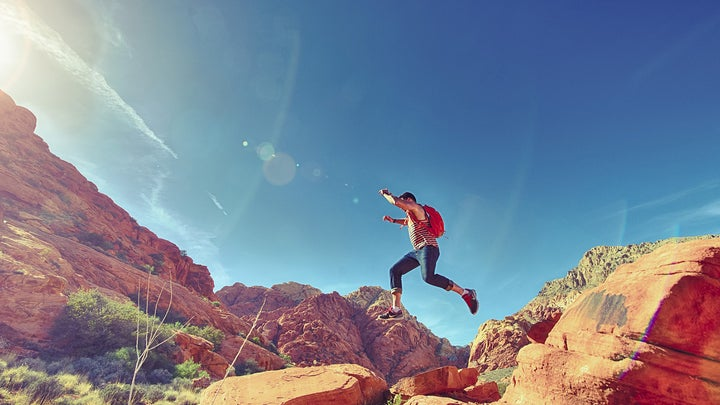 man jumping down red rocks
