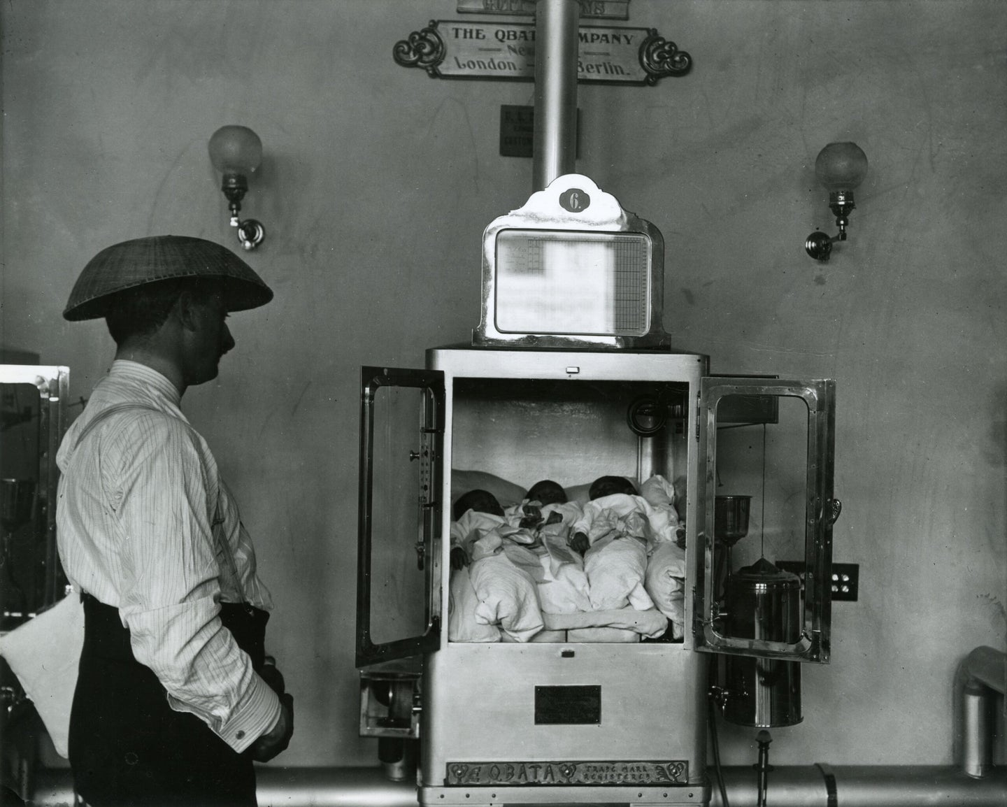 a man looks at several babies in an incubator