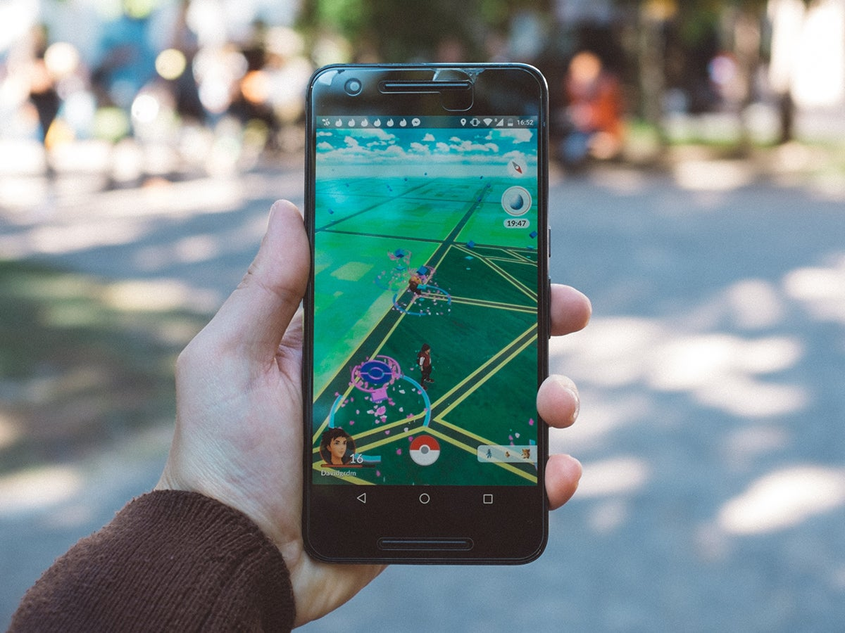 A person holding a phone with Pokemon Go on the screen, while walking on a sidewalk in a park.